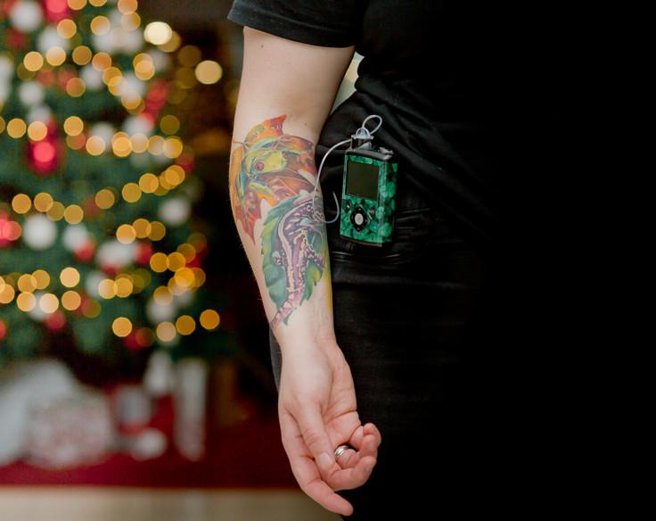 Frau mit Tattoo am Arm und Insulinpumpe