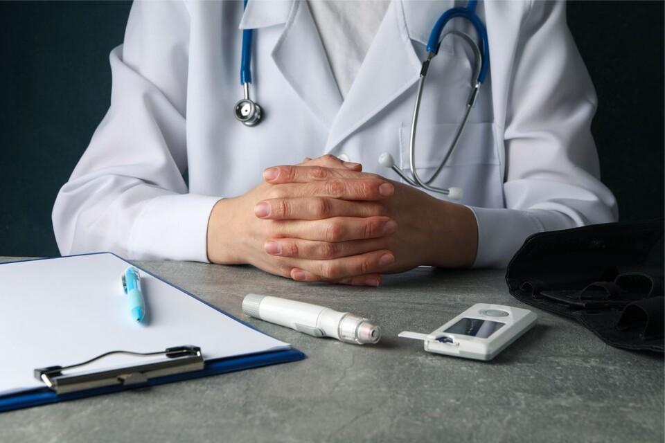 Diabetesarzt sitzt am Tisch