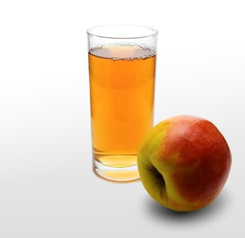 Glas Apfelsaft, daneben liegt ein Apfel