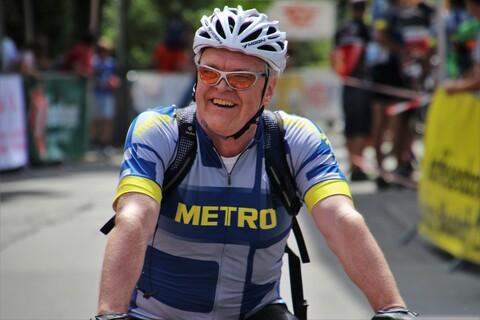Älterer lächelnder Profiradfahrer mit Fahrradhelm.