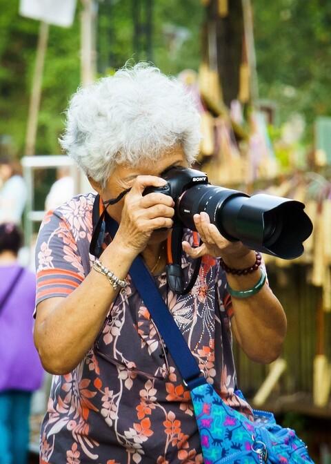 Ältere Dame mit großem professionellen Fotoapparat macht Fotos bei einer Auslandreise.