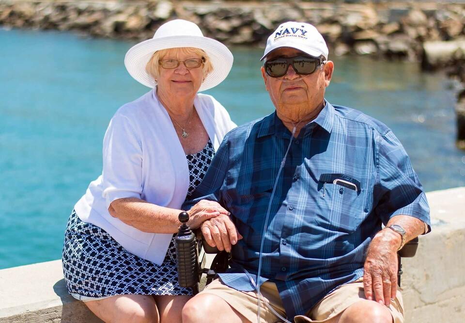 Älteres Eheparr sitzt auf der Bank. Er hat ein Sauerstoffgerät.