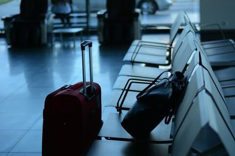 Koffer und Tasche auf der Sitzbank liegend auf dem Flughafen