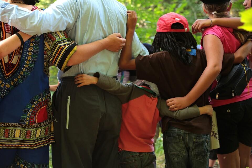 Menschen verschiedener Kultur stehen freundschaftlich zusammen.
