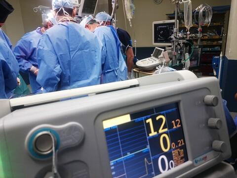 OP-Saal, Chirurgen in blauen Kittel stehen um einen Patieten herum.
