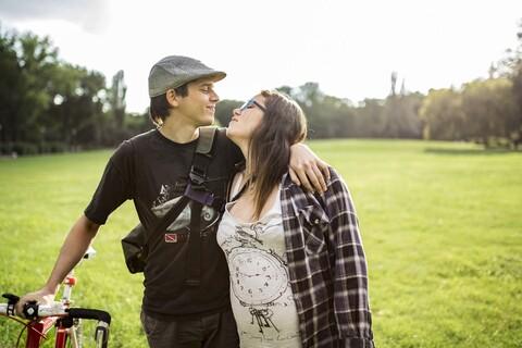 Junge zukünftige Eltern mit Fahrrad auf einer grünen Wiese