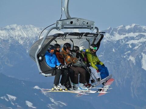 Skifahrer im Lift sitzend in den Alpen - Urlaubszeit
