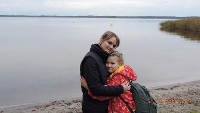 Eine Frau und ein Mädchen umarmen sich lächelnd.