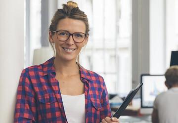 Im Büro stehend lächelt eine Junge Frau mit Brille und kariertem Hemd