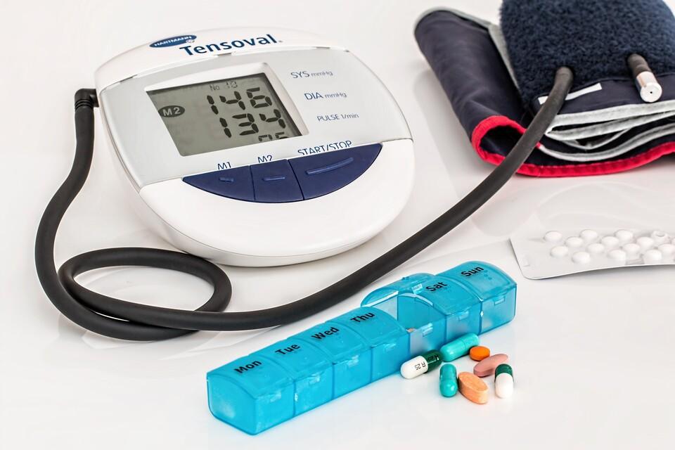 Medikamente, Medikamentenbox und Blutdruckmessgerät liegen auf dem Tisch.