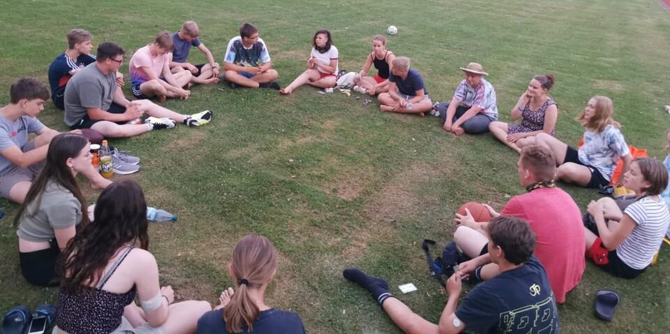 Sommercamp Lübeck Teilnehmer sitzen auf der Wiese im Kreis