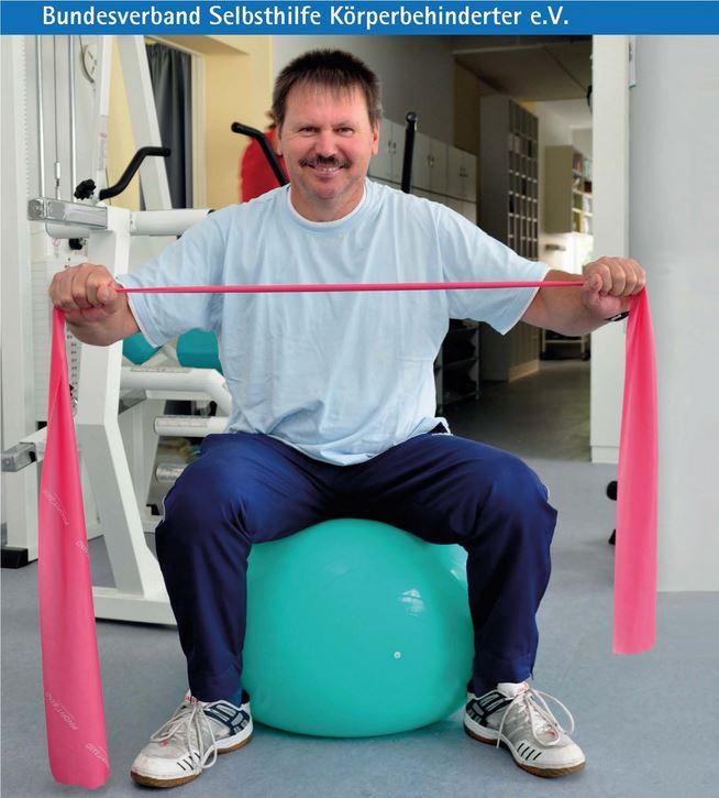 Man sitzt auf einem großen Gymnastikball, macht Übung mit einem rosa Gummiband.