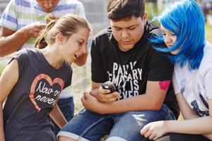 Drei Jugendliche schauen sich Blutzuckerwerte im Display an.